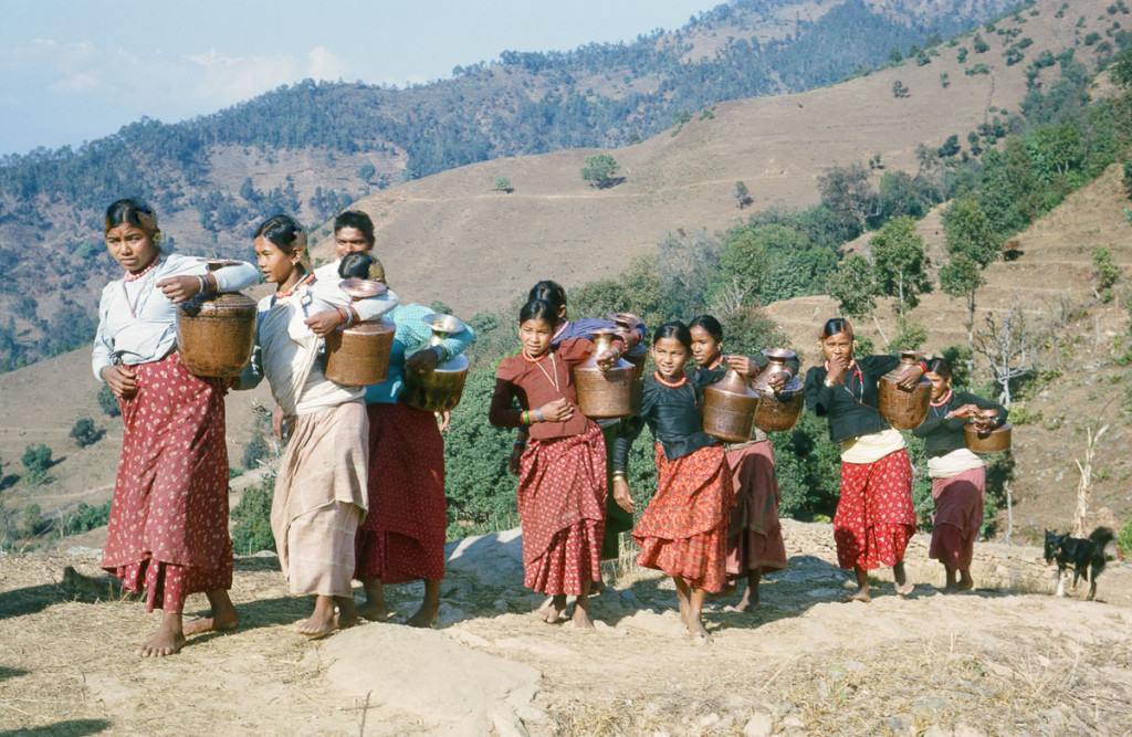 Date: 1964-03 Location: Majhthana, Kaski Description: Brahmin (Bahun) women bringing water up to their village in the dry season. The water source was farther from the village at that time of year, down closer to the Madi Khola. The trail leveled out here and they began singing folk songs.